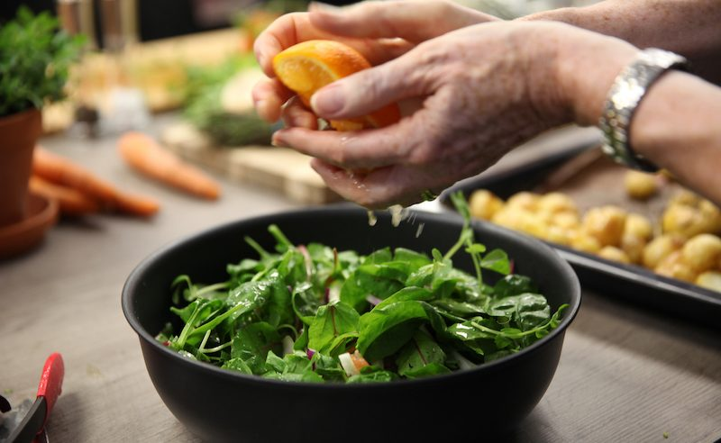 Image of adding dressing to a salad at Food Sorcery Cook School Didsbury