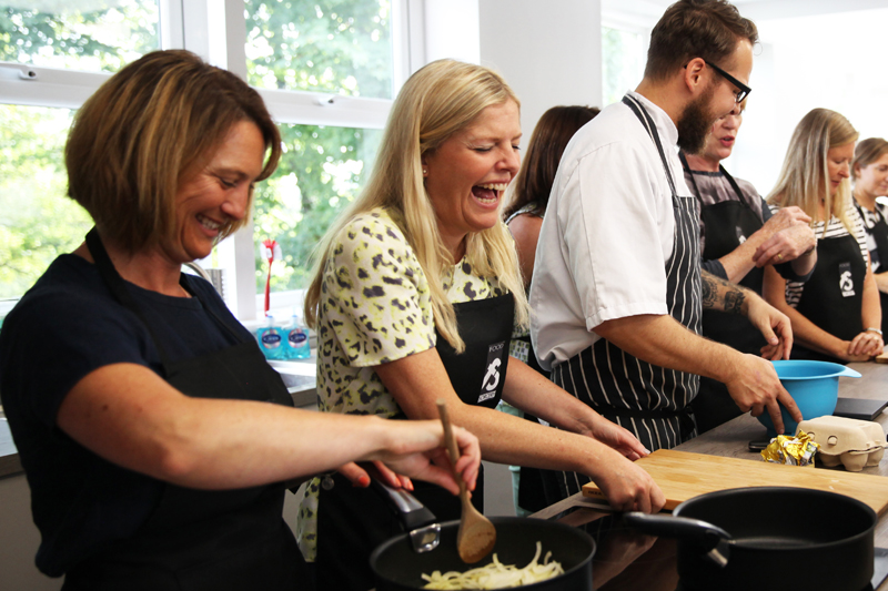 Image of people laughing whilst cooking at food sorcery didsbury