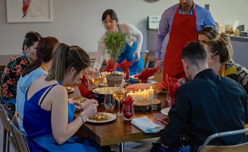 image of people eating at the dining table at Food Sorcery Cookery School Didsbury