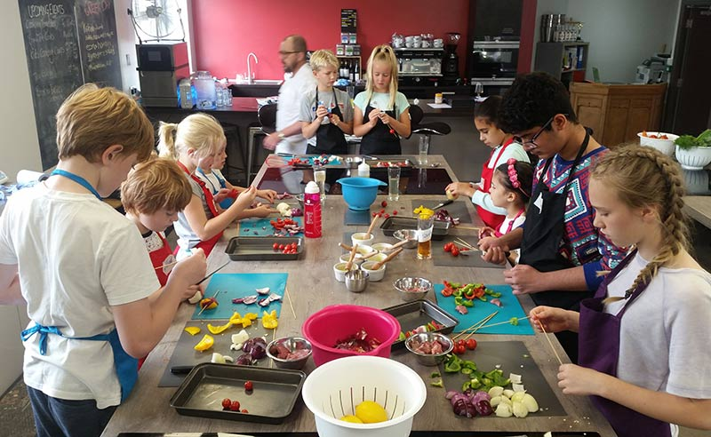 image of kids making keebabs at cookery camp things to do in Manchester cookery holidays
