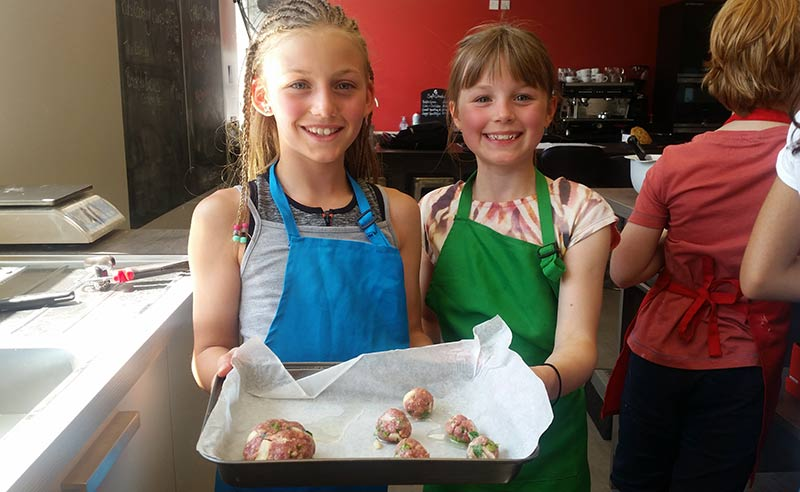 image of happy girls cooking meat balls at kids holiday cookery camp Manchester Didsbury