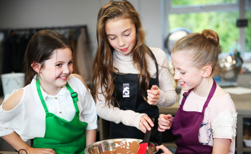 image of three girls cooking at school camp in Didsbury