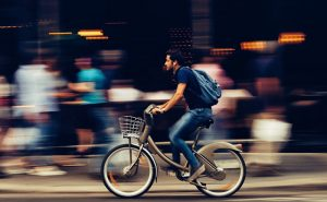 image of man cycling down busy street