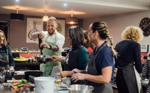 Image of Fit Food Class Chef Jan Cron pouring oil into chimichurri marinade for steak at Food Sorcery, Didsbury