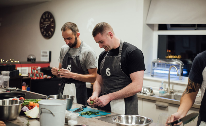 image of Fit Food Class men cooking together preparing ingredients at Food Sorcery Didsbury