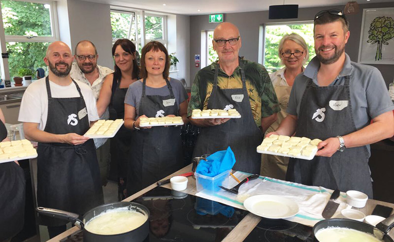 image of chesse making class attendees at Food Sorcery Didsbury with cutting the curd