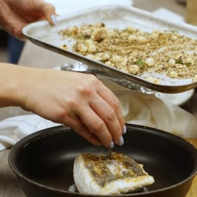 Image of Muscle Gain Fit Food Class participant sprinkling toasted macadamia nuts on cod